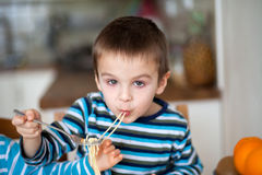 Cute little boy, eating spaghetti at home for lunchtime Stock Photo
