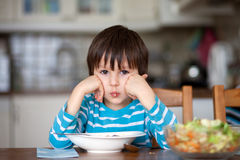 Cute little boy, eating spaghetti at home for lunchtime Royalty Free Stock Images