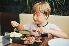Cute little boy eating steak in restaurant royalty free stock image