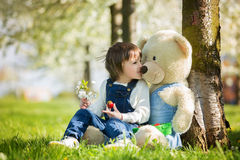 Cute little boy, eating strawberry in the park on a spring sunny. Afternoon, together with his big teddy bear Royalty Free Stock Images