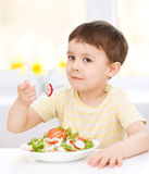 Cute little boy is eating vegetable salad Stock Images