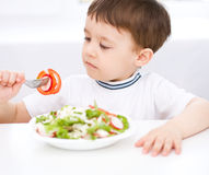 Cute little boy is eating vegetable salad Stock Photography