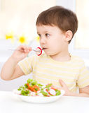 Cute little boy is eating vegetable salad Stock Photos