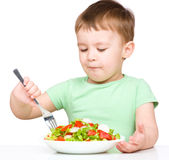 Cute little boy is eating vegetable salad Stock Photo