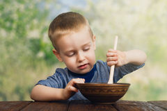 Cute little boy eats outdoors Stock Photos