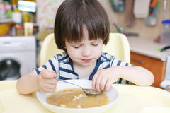 Cute little boy eats pea soup Royalty Free Stock Photo