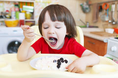 Cute little boy eats quark with berry Stock Photography