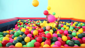 Cute little boy emerging from ball pool