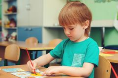 Cute little boy engaged in art and craft in classroom . Cute little boy engaged in art and craft in a classroom royalty free stock photography