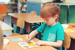Cute little boy engaged in art and craft in classroom . Learning and education concept. Cute little boy engaged in art and craft in a classroom . Learning and stock photos