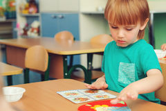 Cute little boy engaged in art and craft in classroom . Learning and education concept. Cute little boy engaged in art and craft in a classroom . Learning and royalty free stock photos