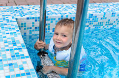 Cute little boy enjoying a swim in a pool Stock Photos