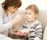 Cute little boy is fed using spoon Stock Photos