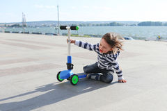 Cute little boy fell off the scooter Royalty Free Stock Photos