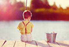 Cute little boy fishing on pond at sunset Stock Photos
