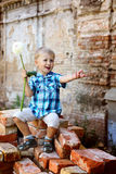 Cute little boy with flouwers sitting on bricks Stock Photo