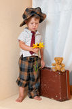 Cute little boy with the flower. He is wearing a hat Stock Images