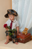 Cute little boy with the flower. Cute little boy with the flower sitting on an old suitcase. He is wearing a hat Royalty Free Stock Images