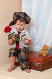 Cute little boy with the flower. Cute little boy with the flower sitting on an old suitcase. He is wearing a hat Stock Photo