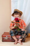 Cute little boy with the flower. Cute little boy with the flower sitting on an old suitcase. He is wearing a hat Stock Photography