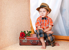 Cute little boy with the flower. Cute little boy with the flower sitting on an old suitcase. He is wearing a hat Stock Photos
