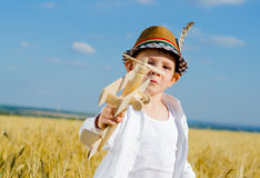 Cute little boy flying his toy biplane Royalty Free Stock Image