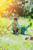 Cute little boy gardening with a watering can in domestic garden. stock photos