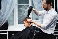 Cute little boy is getting haircut by hairdresser at the barbershop stock photo