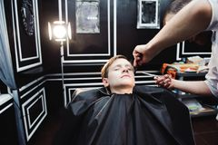 Cute little boy is getting haircut by hairdresser at the barbershop. royalty free stock photos