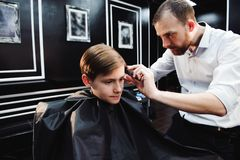 Cute little boy is getting haircut by hairdresser at the barbershop. stock photos