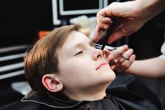 Cute little boy is getting haircut by hairdresser at the barbershop. royalty free stock photo