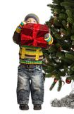 Cute little boy with gift near Christmas tree Stock Photos