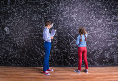 Cute little boy and girl in front of a big blackboard. Royalty Free Stock Images