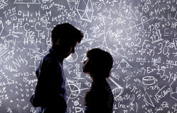Cute little boy and girl in front of a big blackboard. Royalty Free Stock Photos