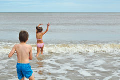 Cute little boy and girl, playing in wave on beach Royalty Free Stock Photography