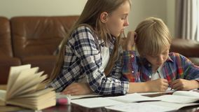 Cute little boy and girl studying at home in the foreground while their mother sitting in the background. Kids doing stock video