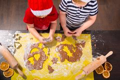 Twins preparing Christmas cookies in the kitchen Stock Photo