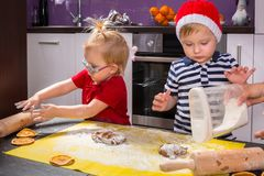 Twins preparing Christmas cookies in the kitchen Stock Images