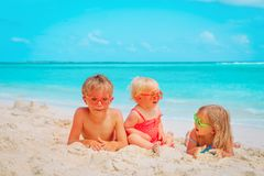 Cute little boy and girls play with sand on beach stock photography