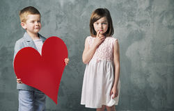 Cute little boy giving a heart to his sister Royalty Free Stock Image