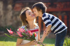 Cute little boy, giving present to his mom for Mothers day. In the garden Stock Images
