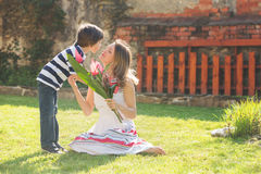 Cute little boy, giving present to his mom for Mothers day Stock Photo