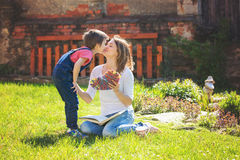 Cute little boy, giving present to his mom for Mothers day in th. E garden, springtime Royalty Free Stock Image