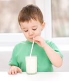 Cute little boy with a glass of milk. Cute little boy is dipping his tongue in the glass of milk Royalty Free Stock Photos