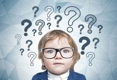 Cute little boy in glasses, many questions. Adorable little boy with blond hair and glasses wearing a suit sitting near geometric pattern wall with many question royalty free stock photography
