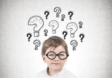 Cute little boy with glasses, questions. Cute little boy in a white shirt is wearing a pair of glasses with a thick frame and thinking while looking at camera. A Stock Photo