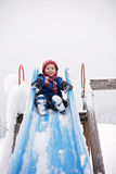 Cute little boy, going down a snowy slide Royalty Free Stock Images