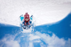Cute little boy, going down a snowy slide Royalty Free Stock Photography