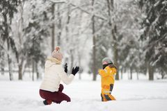 Cute little boy and grandma / babysitter / mother playing snowballs in winter Park. royalty free stock photo