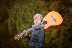 Cute little boy with guitar in nature background. He is dressed Stock Photography